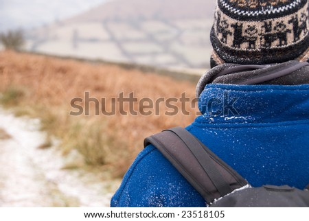 Partial view of a hiker wearing fleece and backpack from behind with snowflakes on his shoulder - stock photo