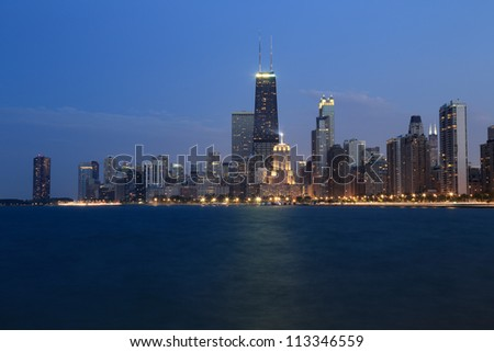 Partial view of the Chicago skyline at dusk from pier along Lake Michigan - stock photo