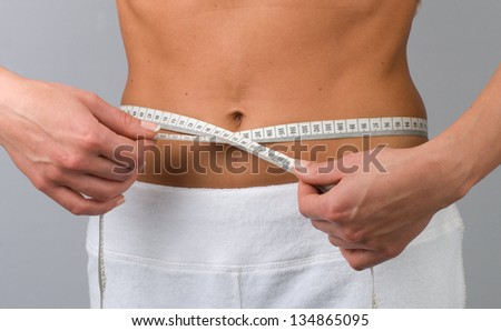 Partial view of young woman holding tape measure around her bare waist - stock photo