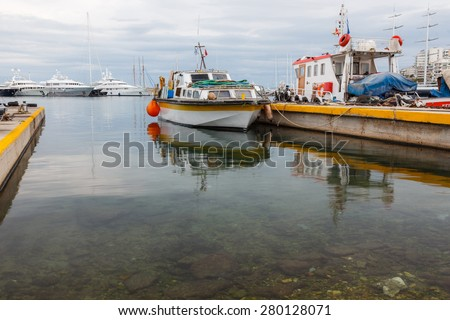 Partial view of Zea Marina port with fishing boats anchored along the shores in Greece