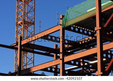 Partially completed high rise office building with crane tower visible. - stock photo