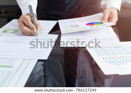 Partially cropped of business man signing his signature on a document with reflection on desktop as a copy space.