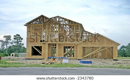 partially framed new home with OSB exterior and sign