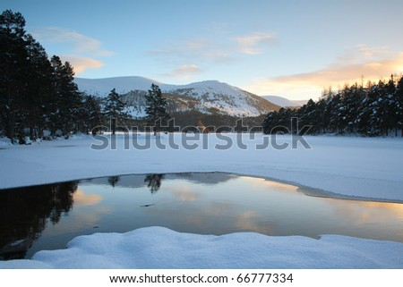 Partially frozen lake. (Loch an Eilean, Scotland. Situated in the Cairngorm National Park.) - stock photo