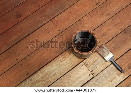 Partially stained deck; a can of stain and a brush divide newly stained area from the old weathered one. - stock photo