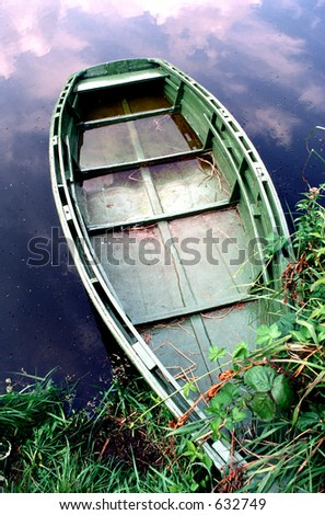 Partially submerged old boat on the shore of the lake - stock photo
