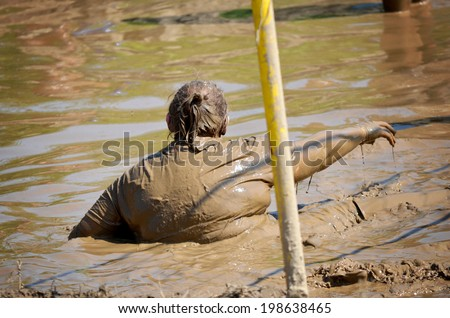 Participant at a mud volleyball tournament - stock photo