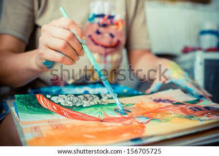 particular of woman painter hand painting in her studio - stock photo