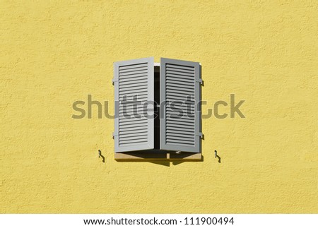 Partly opened gray window shutters on bright yellow wall