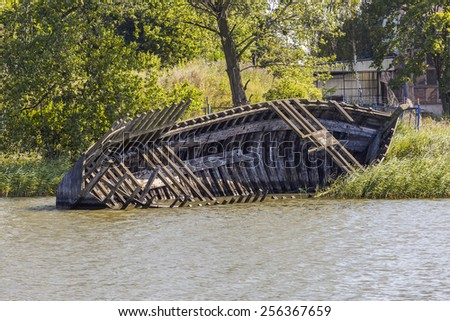 Partly submerged old wooden boat - stock photo