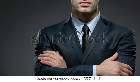Partly viewed man wearing business suit and black tie with arms crossed - stock photo