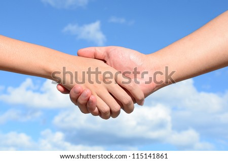 Partner hand between a man and a woman on blue sky background, Teamwork - stock photo