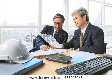 partner of senior engineering working man serious meeting about project discussing solution shot on table in office meeting room  - stock photo
