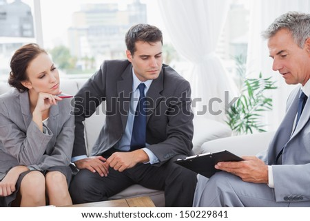 Partners analyzing documents during a meeting in cosy meeting room - stock photo