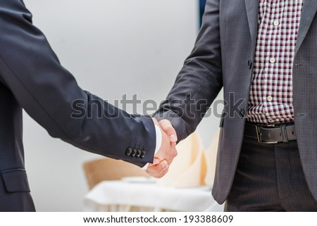 Partners meeting! Two young businessman standing opposite each other and shake their hands. Young people smiling into the camera. Close-up view below