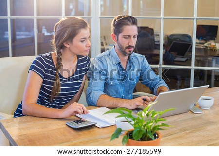 Partners working at desk using laptop in the office - stock photo