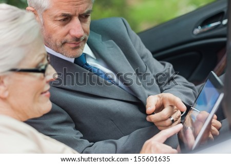 Partners working together on tablet in classy convertible on a bright day - stock photo