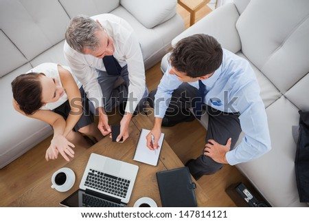 Partners working while having a coffee together in cosy meeting room