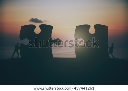 Partnership concept with businesspeople silhouettes putting puzzle pieces together on sunset background - stock photo