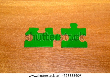 Partnership concept with puzzle pieces together on wooden background.
