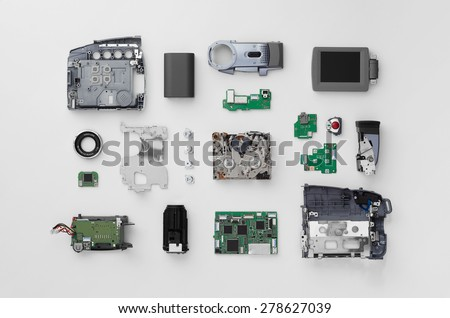 Parts of a mini DV video camera separate and well arranged over white background, above view - stock photo