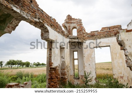 Parts of a ruined house with dramatic sky - different textures and herbs - stock photo