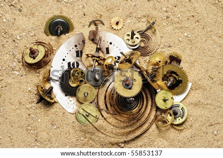 parts of clockwork mechanism on the sand - stock photo