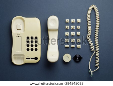 Parts of vintage home telephone well organized over dark blue background, above view. This image is part of a larger series.