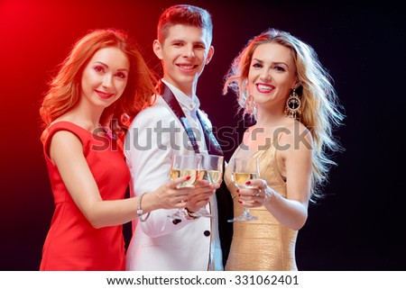 Party and celebration. Group of three happy smiling friends toasting with wineglasses having fun together in night club.