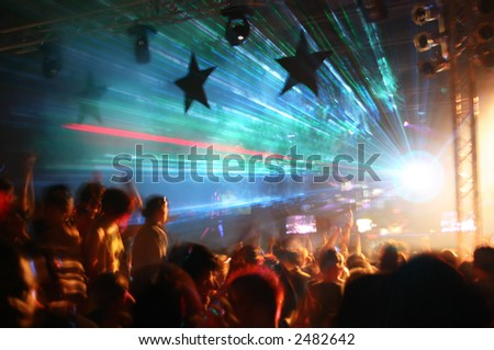 Party at Disco concert full of young people dancing in music and laser show - stock photo