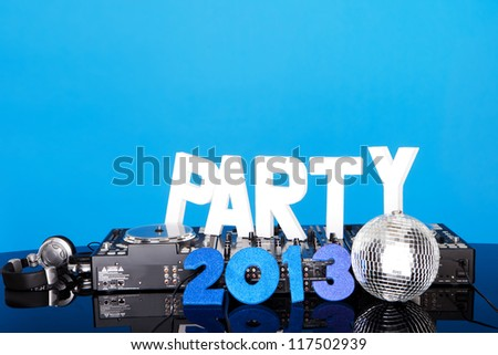 PARTY 2013 background with DJ music mixing deck, mirrored disco ball and lettering against a blue background with copyspace - stock photo