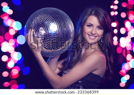 Party, celebration concept. Toned image of beautiful woman in evening dresses holding disco ball over holidays lights bokeh beackground - stock photo