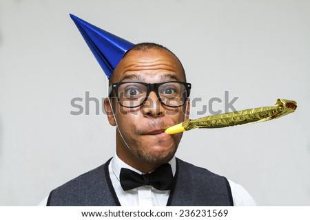 Party celebration with this young geek with a hat and party blower. Christmas, office or birthday concept - stock photo