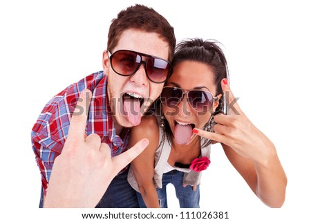 party couple screaming and showing rock and roll sign while sticking their tongues out. against a white background - stock photo