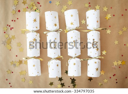 Party cracker with 2016 written on them and glittery confetti - stock photo