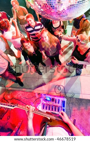 Party crowd around a stage with a guitarist performing - stock photo