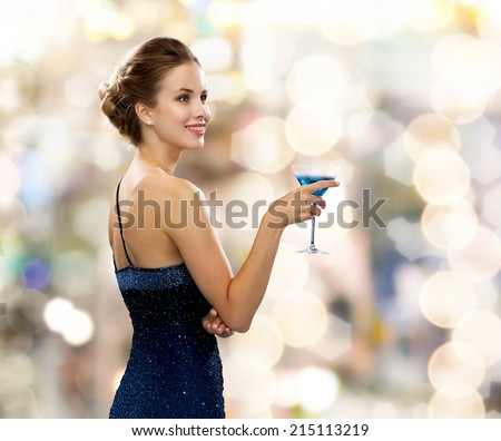 party, drinks, holidays, luxury and celebration concept - smiling woman in evening dress holding cocktail over lights background - stock photo