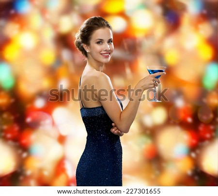 party, drinks, holidays, luxury and celebration concept - smiling woman in evening dress holding cocktail over red lights background - stock photo