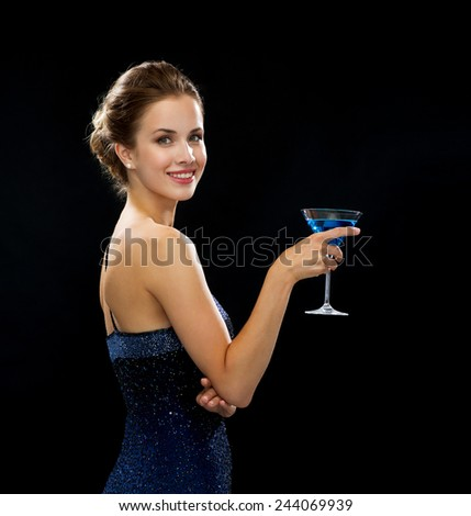 party, drinks, holidays, luxury and celebration concept - smiling woman in evening dress holding cocktail over black background - stock photo