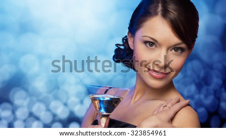 party, drinks, holidays, luxury and celebration concept - smiling woman in evening dress holding cocktail over blue lights background - stock photo