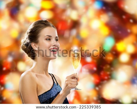 party, drinks, holidays, luxury and celebration concept - smiling woman in evening dress with glass of sparkling wine over red lights background