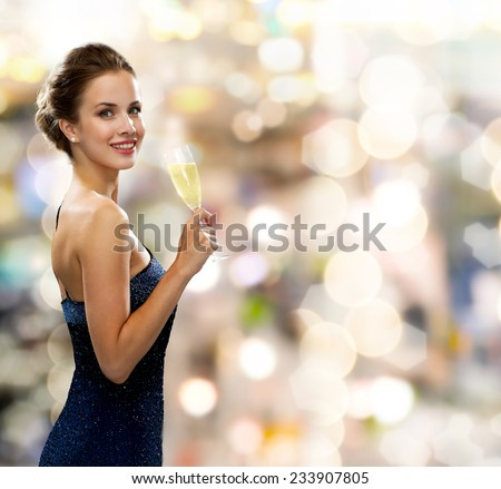 party, drinks, holidays, luxury and celebration concept - smiling woman in evening dress with glass of sparkling wine over lights background - stock photo