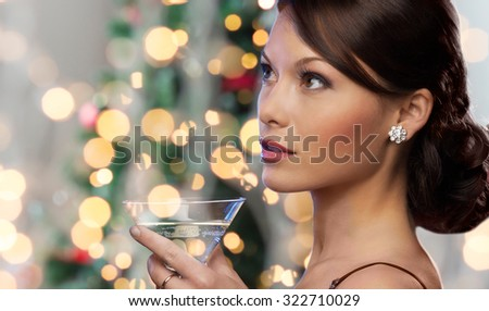 party, drinks, holidays, luxury and celebration concept - woman face with cocktail over christmas tree lights - stock photo