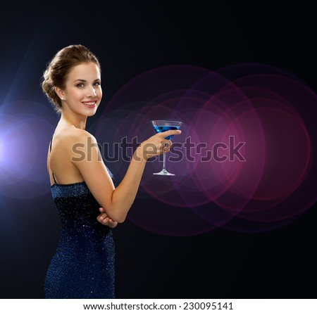 party, drinks, holidays, people and celebration concept - smiling woman in evening dress holding cocktail over night lights background - stock photo