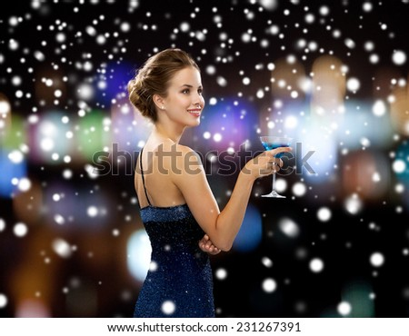 party, drinks, holidays, people and christmas concept - smiling woman in evening dress holding cocktail over night lights and snow background - stock photo
