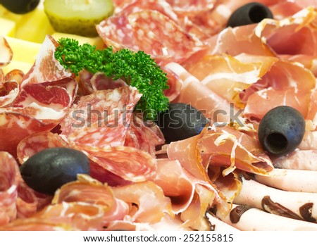 Party food with sausage slide, ham, olive, decorated with green parsley (manual focus) - stock photo