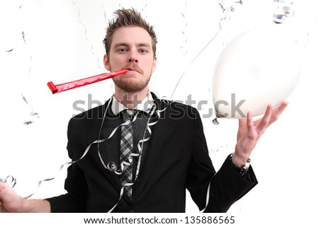 Party guy with partyhat and party blower. Wearing a suit. White background. - stock photo