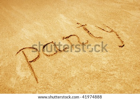 Party handwritten in sand on a beach
