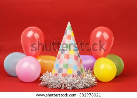 Party hat and party balloons on red background - stock photo