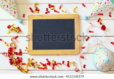 Party hat next to colorful confetti and empty blackboard on wooden table. Top view - stock photo